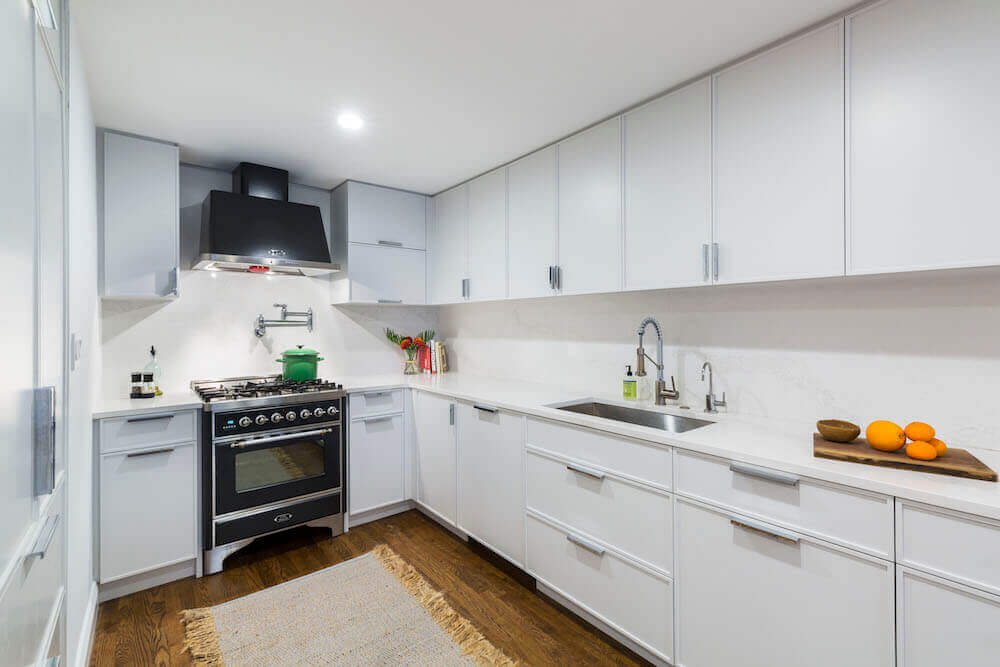 Image of a kitchen with glossy white kitchen cabinets, wooden floor and black range