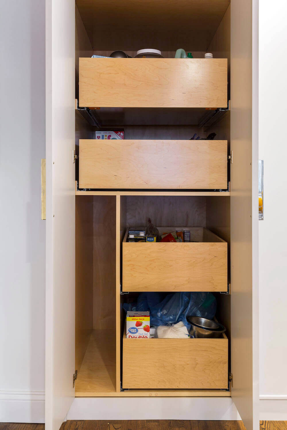 Image of an open kitchen cabinet with wooden pull-out drawers