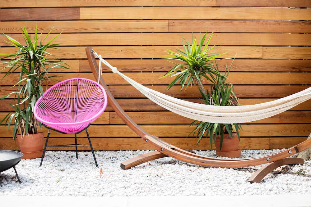 Image of a renovated backyard with cedar walls, gravel floor and hammock area