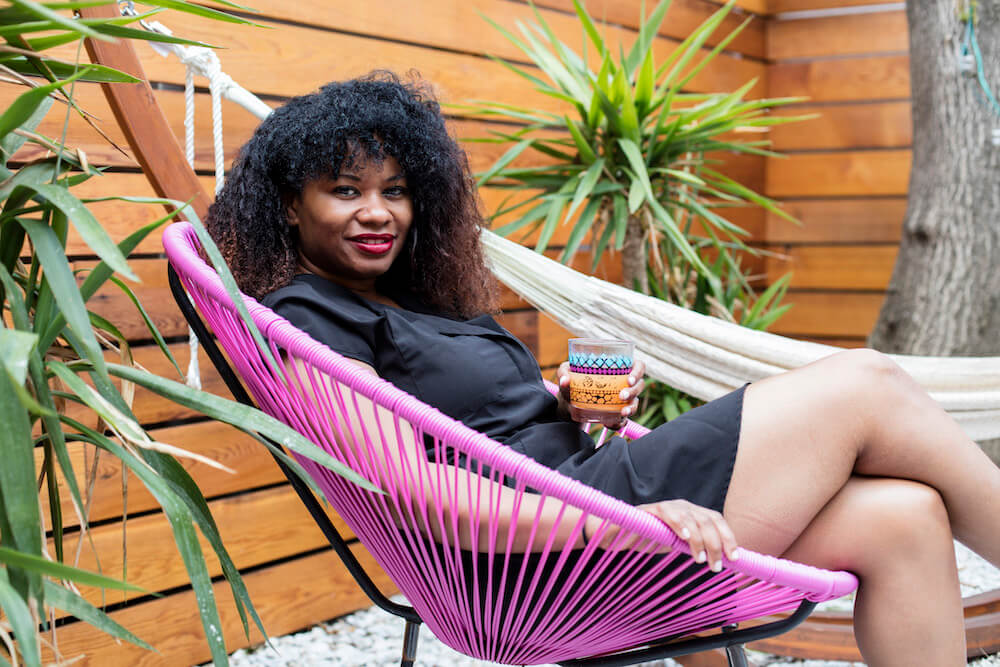 Image of a Sweeten homeowner sitting in her renovated backyard
