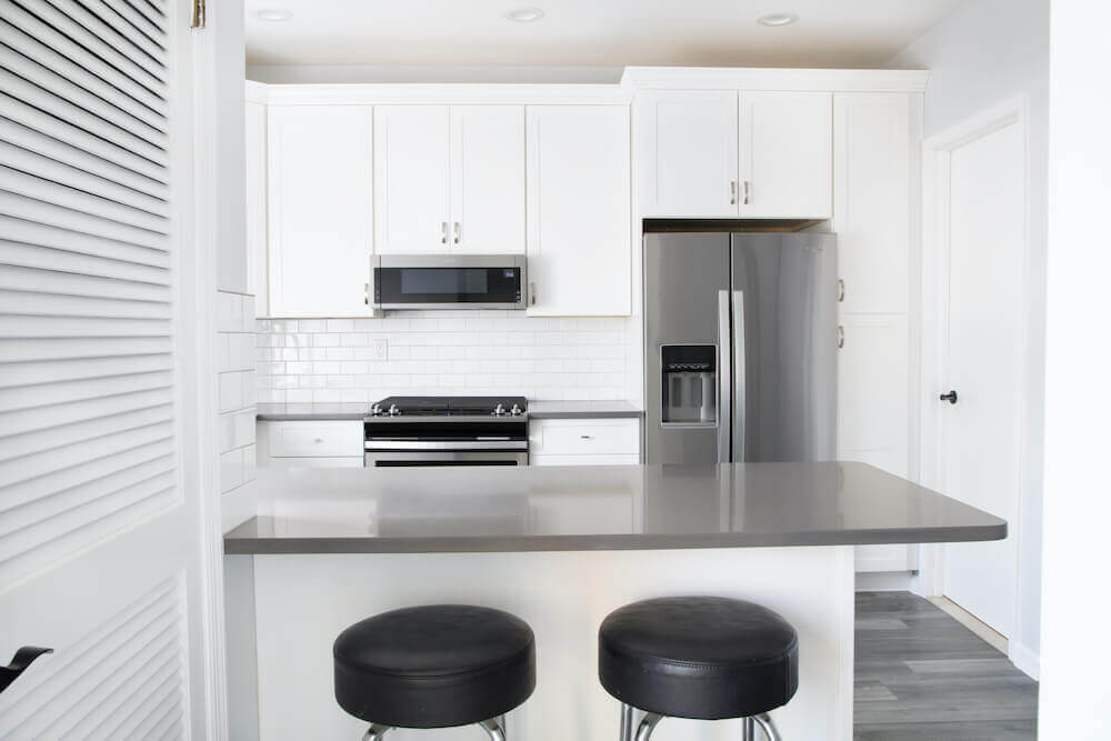 Image of a kitchen peninsula with black bar stools facing into the kitchen area