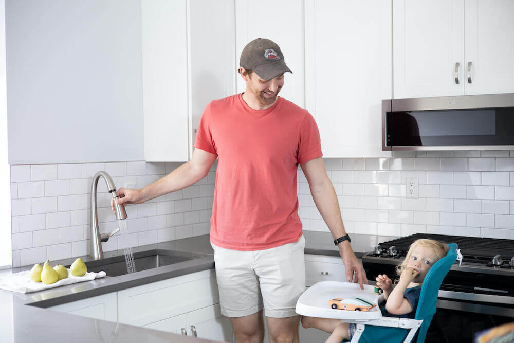 Image of a father feeding a baby in a high chair by a white kitchen sink
