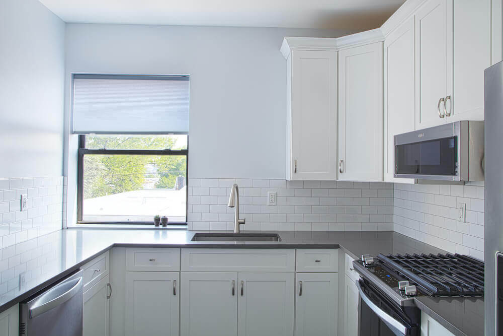 Image of a small kitchen area with white cabinets and white subway tile walls