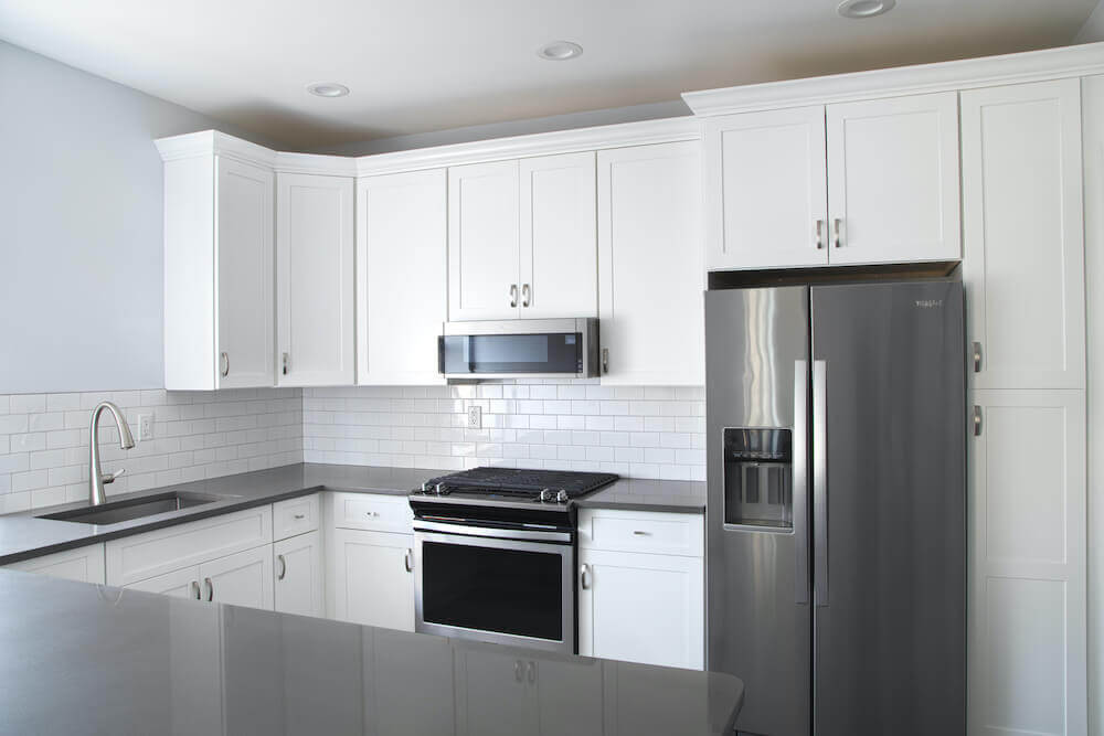 Image of a renovated white kitchen with gray countertops and silver fridge