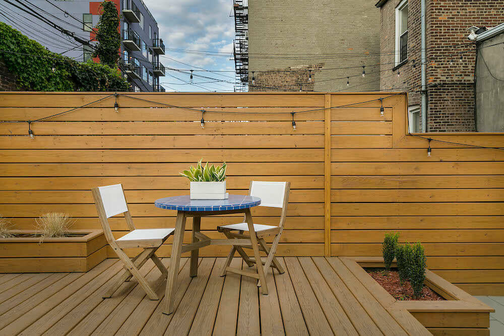 Image of a wooden backyard deck with cafe seating