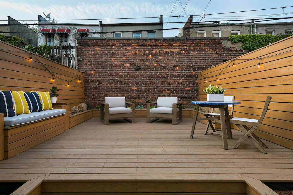 Image of a backyard remodel with bench seating and wood walls