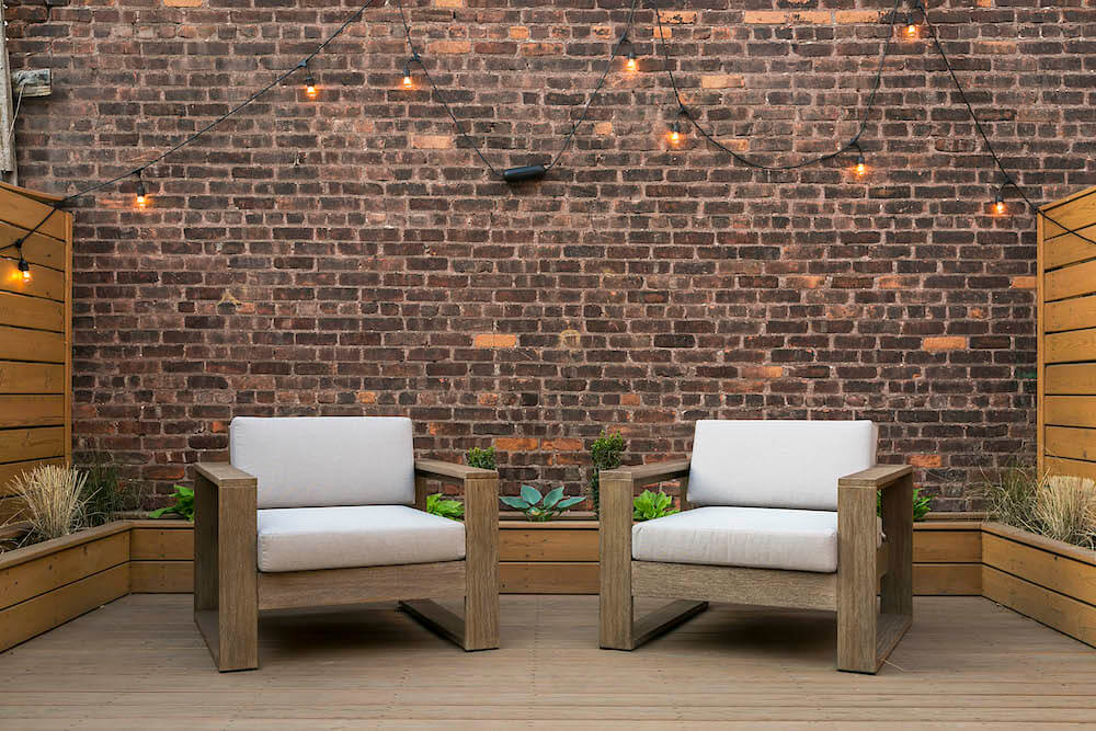 Image of two outdoor chairs with exposed brick wall