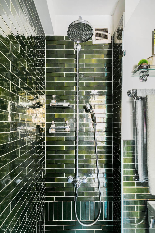 Image of vintage shower head in green tile shower