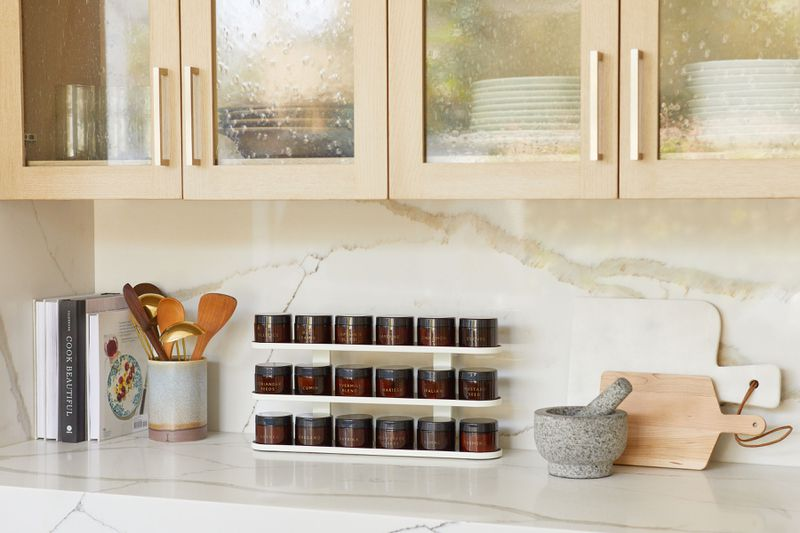 A modern spice rack in amber bottles sits on a modern kitchen counter.