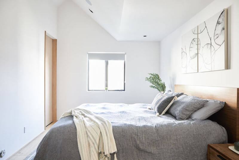 Minimalist master bedroom with slanted white ceiling and walls