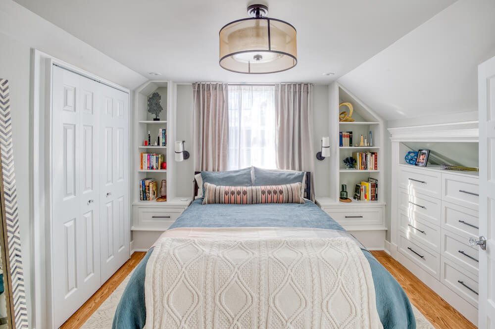 Attic master bedroom with custom built-in shelves surrounding bed