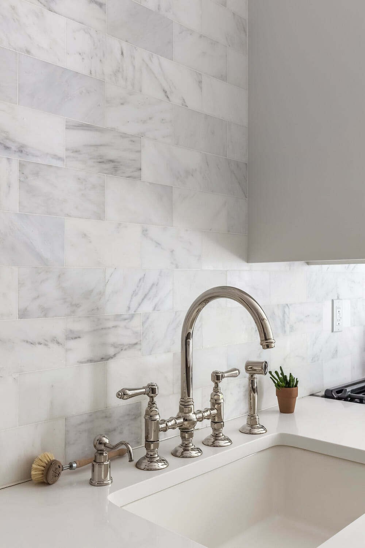 Image of a kitchen sink with Carrara marble backsplash