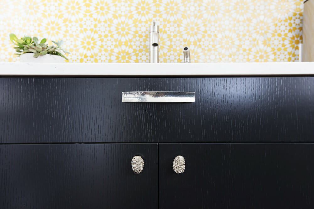 Image of a closeup black cabinet with silver cabinet handles