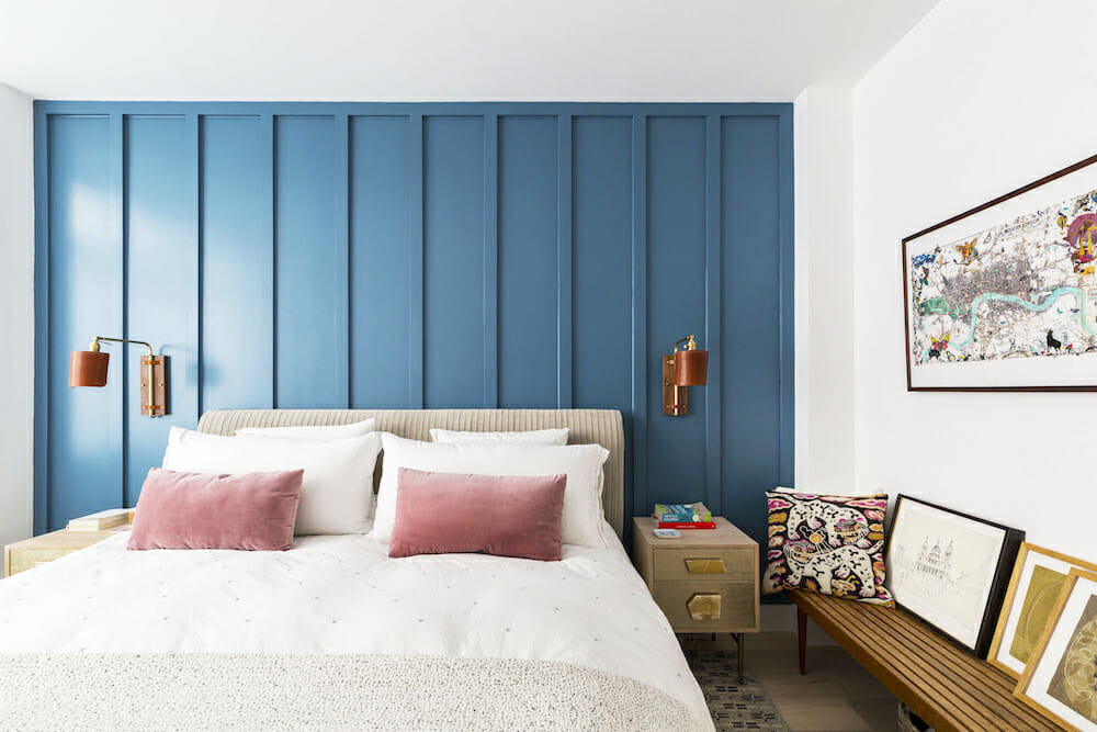 master bedroom with blue paneled accent wall behind bed