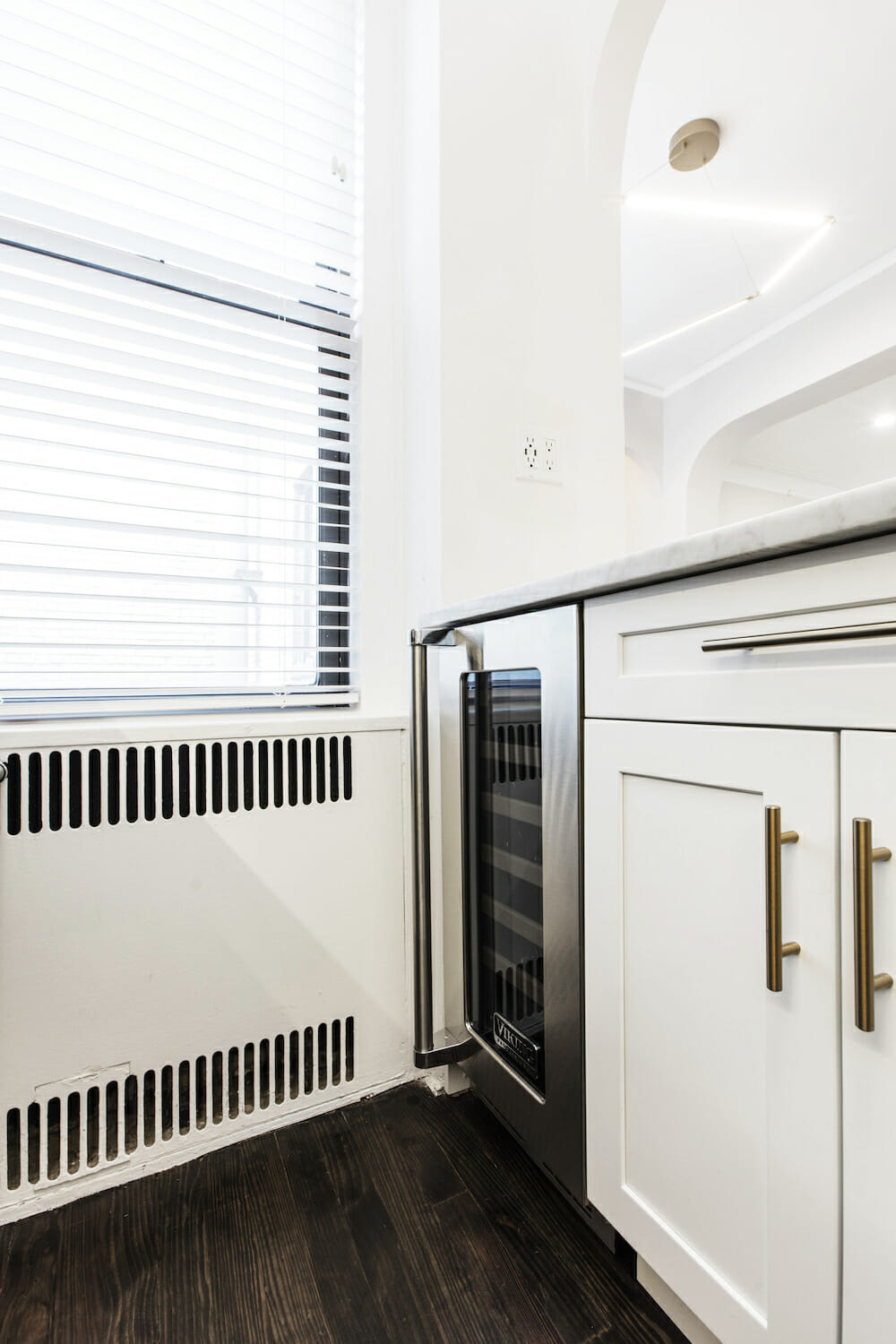 Image of white kitchen cabinets with a wine refrigerator