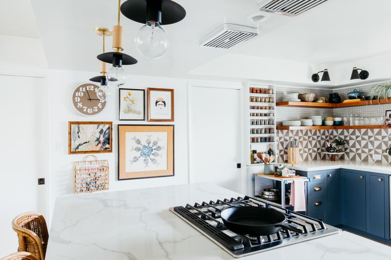 a kitchen with open shelving and a color coordinated spice rack.