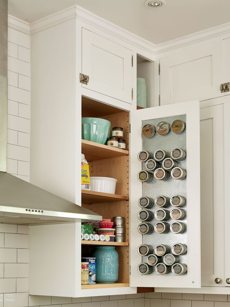 A magnetic spice rack inside a kitchen cabinet.