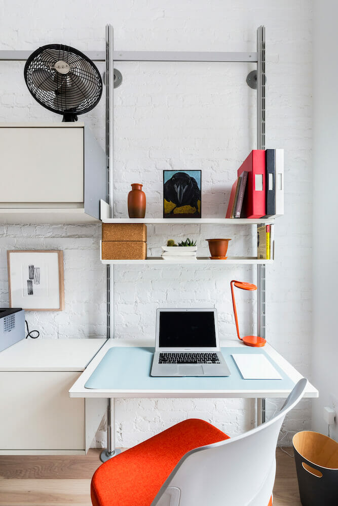 Image of an at-home workspace with metal desk and white hanging shelves