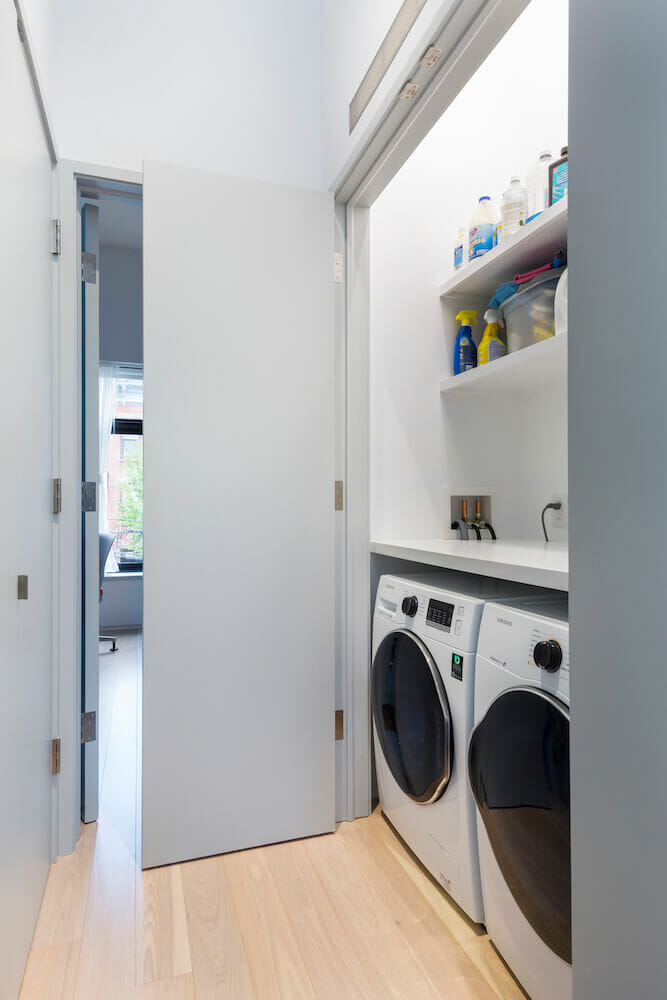 Image of a laundry closet with washer, dryer and shelves of cleaning products