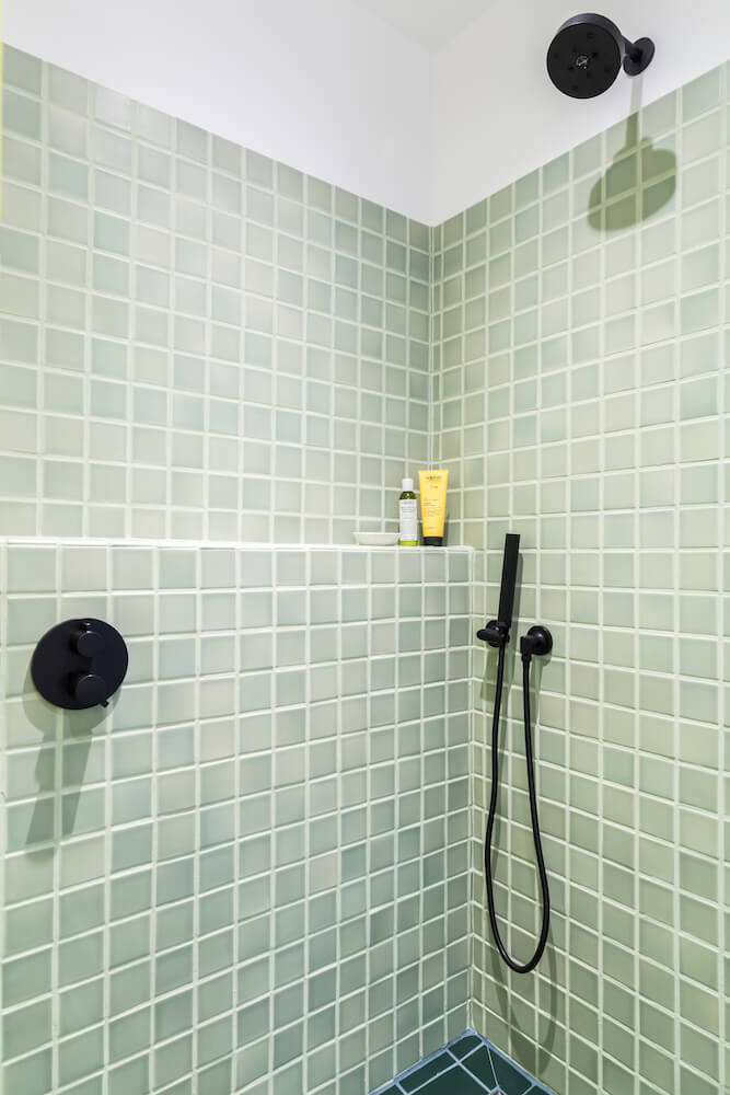 Image of a shower with light green tiles, black fixtures and shelf for bathroom supplies