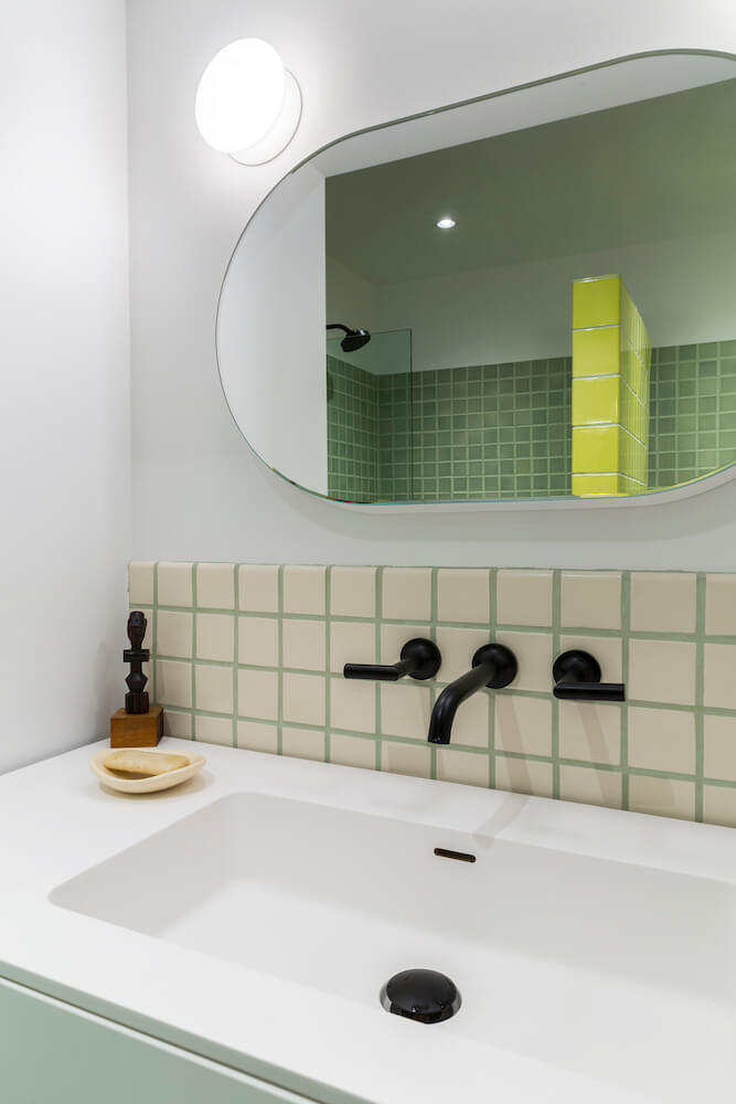 Image of a bathroom vanity with black fixtures and modern oval mirror