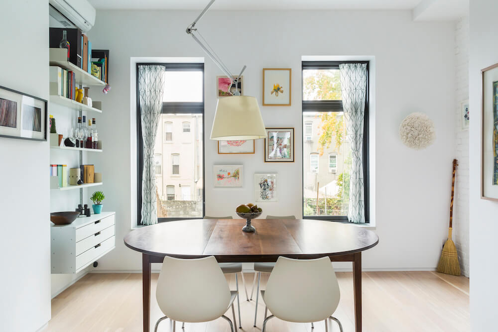 Image of a dining area with wooden dining table, chairs and wall shelves