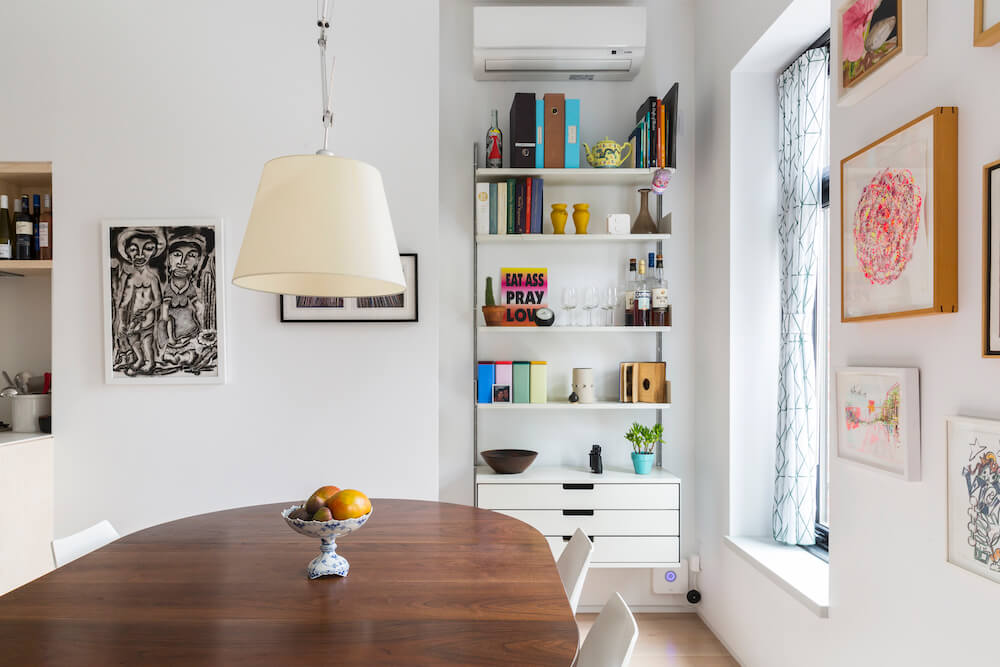 Image of a dining area with wooden table, hanging pendant lamp and shelving unit