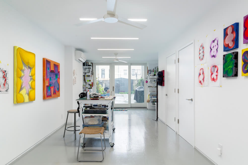 Image of an at-home basement art studio with hanging art on the walls