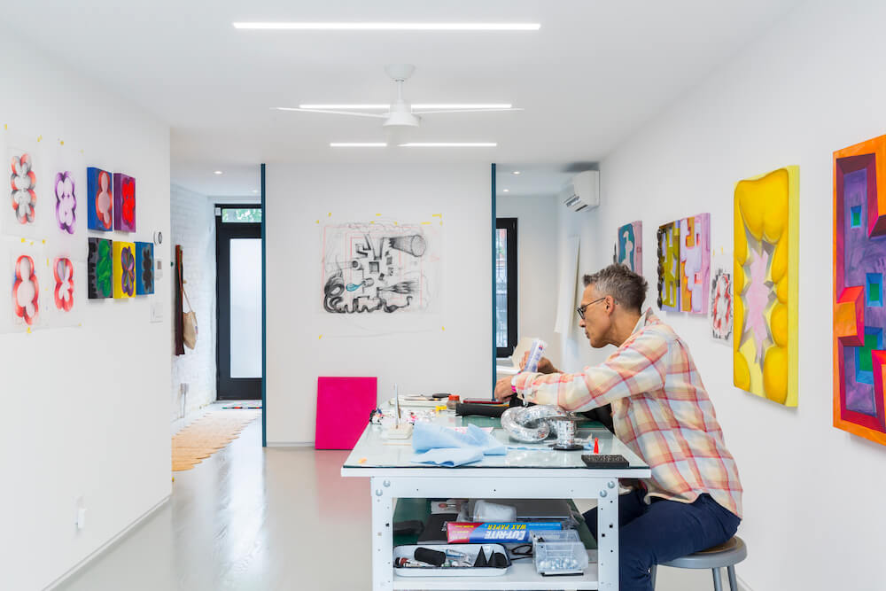 Image of a Sweeten renovator sitting in his at-home art studio working at a crafts table