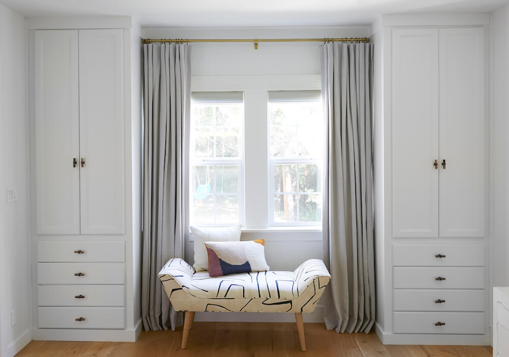 custom built-in closets in bedroom with lounging bench by window