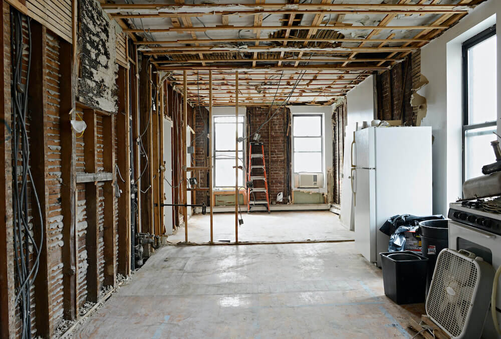 A home during a gut renovation with walls removed and foundation exposed