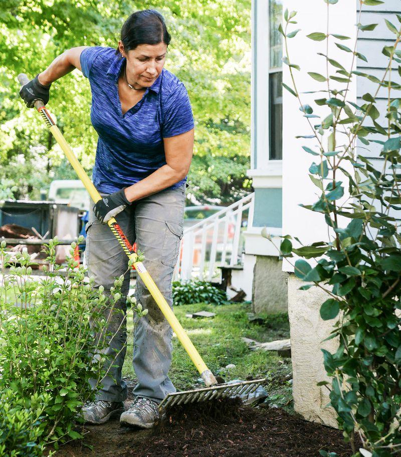 Fall 2021 Landscaping, Fall prep, Jenn Nawada breaks up compacted mulch with a rake