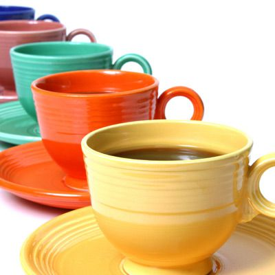Colorful ceramic mugs lined up in a row.