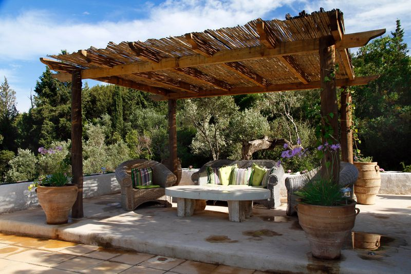 A stand along pergola with a thatched roof to provide extra shade.