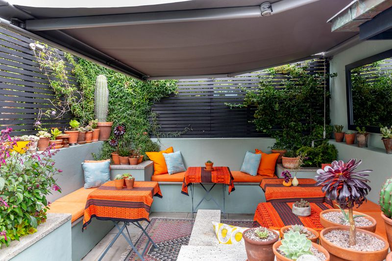 An outdoor sitting area with orange accents and a gray fabric canopy overhead.