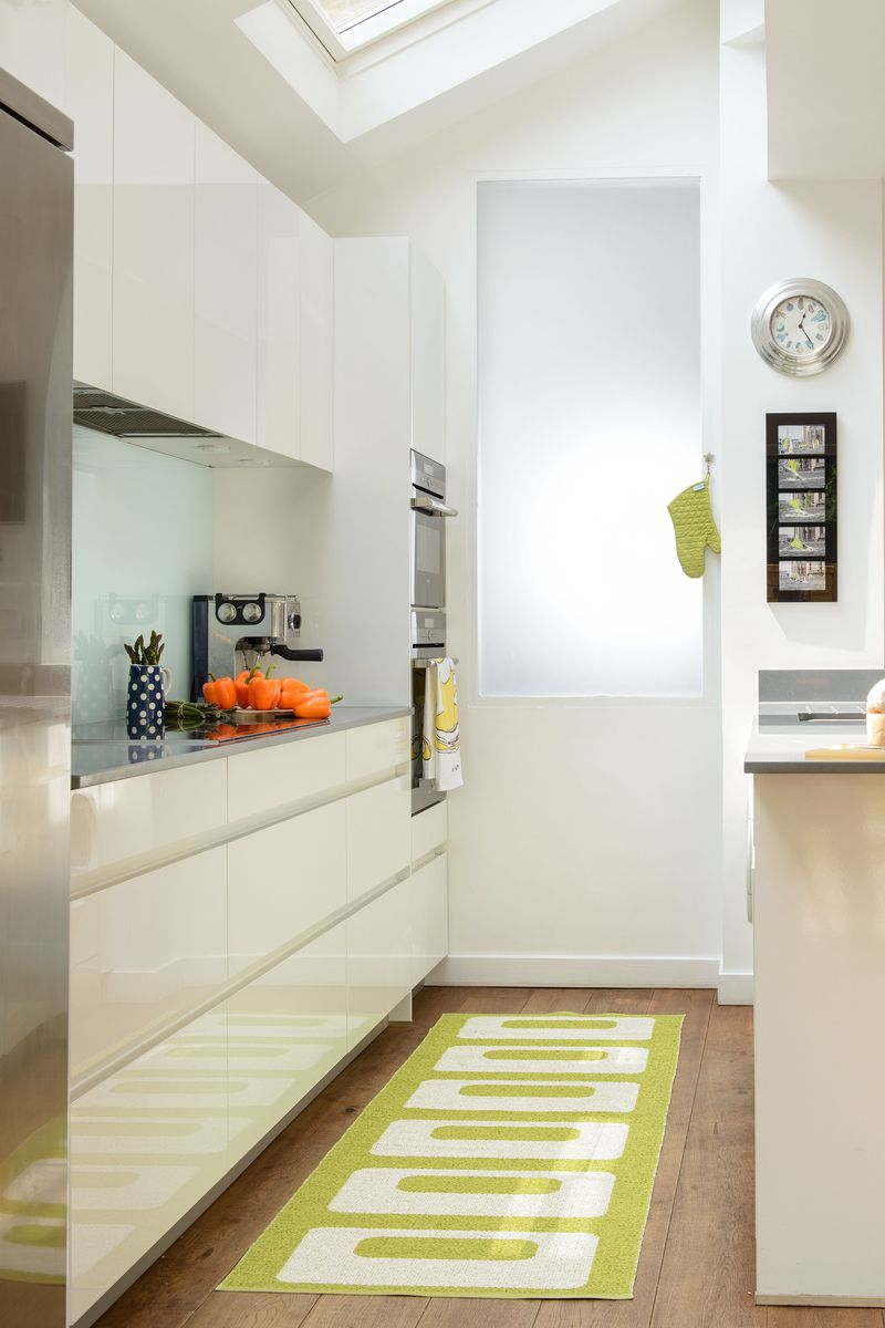 A minimalist galley kitchen with white cabinets and a bright green rug.