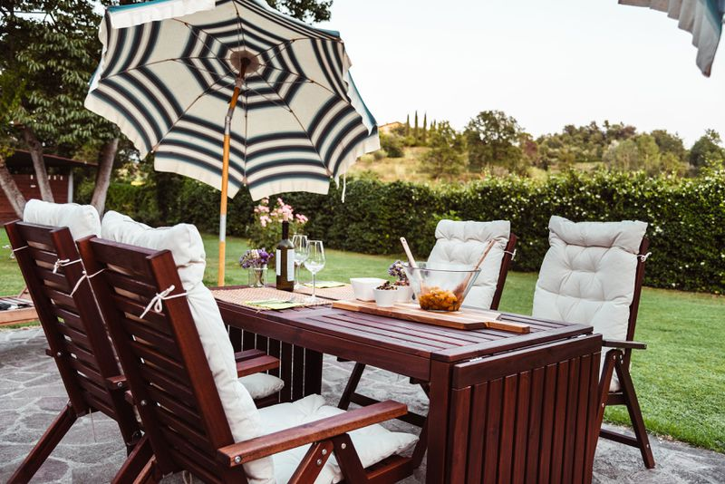 An outdoor patio with a seating area and a tilted umbrella to provide shade.